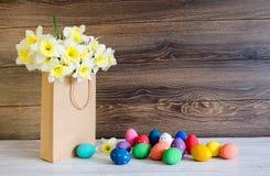 Oeufs de pâques colorés avec le beau bouquet du narcisse dans un sac de papier sur le fond en bois images stock