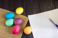 Oeufs de pâques colorés avec le papier blanc et le stylo sur t en bois rustique Images stock