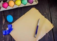 Oeufs de pâques colorés avec le vieux papier blanc et stylo sur le bois rustique Images stock