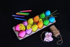 Oeufs de pâques colorés avec les marqueurs colorés, la corde et les fleurs jaunes de ressort Image stock