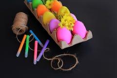 Oeufs de pâques colorés avec les marqueurs colorés, la corde et les fleurs jaunes de ressort Photos libres de droits