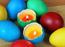 Oeufs de pâques colorés, bougie, flamme Photographie stock
