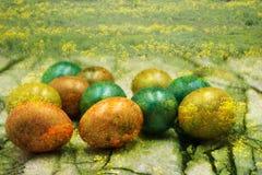 Oeufs de pâques colorés cachés dans les fleurs et l'herbe images libres de droits