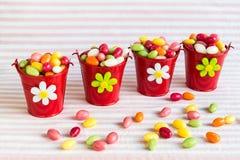 Oeufs de pâques colorés dans des seaux rouges Image stock