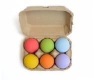 Oeufs de pâques colorés dans le carton d'oeufs Images stock