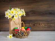Oeufs de pâques colorés dans le panier avec le beau bouquet du narcisse dans le sac de papier sur le fond en bois Photos stock