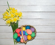 Oeufs de pâques colorés dans le panier avec le beau bouquet du narcisse sur le fond en bois images libres de droits