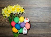 Oeufs de pâques colorés dans le panier avec le beau bouquet du narcisse sur le fond en bois photo libre de droits