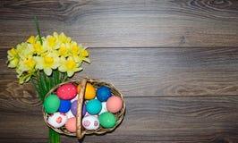 Oeufs de pâques colorés dans le panier avec le beau bouquet du narcisse sur le fond en bois images stock