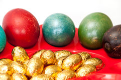 Oeufs de pâques colorés dans le panier avec les oeufs de pâques d'or de chocolat Photographie stock