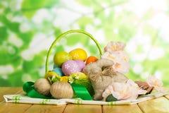 Oeufs de pâques colorés dans le panier, cordes entrelacées, lapin, fleurs Images libres de droits