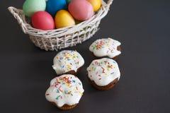 Oeufs de pâques colorés dans le panier et petits gâteaux doux de petits pains sur un fond noir le fond a coloré le vecteur rouge  Photo stock