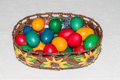 Oeufs de pâques colorés dans le panier Joyeuses Pâques, religiou chrétien Photographie stock