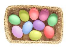 Oeufs de pâques colorés dans le panier sur le fond blanc Images stock