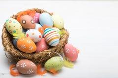 Oeufs de pâques colorés dans le panier sur un fond blanc Pâques Photographie stock