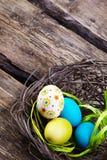 Oeufs de pâques colorés dans un nid sur le fond en bois Photos stock