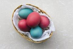 Oeufs de pâques colorés dans un panier Photo libre de droits