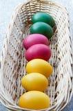 Oeufs de pâques colorés dans un panier Photographie stock