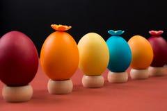 Oeufs de pâques colorés dans une rangée, oeufs de pâques décorés sur le fond noir Image stock