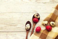 Oeufs de pâques colorés de cailles dans des cuillères en bois Image libre de droits