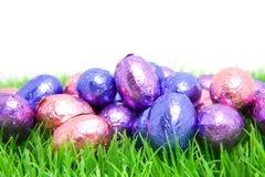Oeufs de pâques colorés de chocolat dans l'herbe Images libres de droits