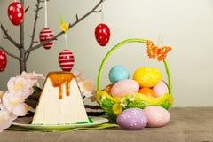 Oeufs de pâques colorés, dessert de gâteau au fromage de Pâques, fleurs sur le gris photo stock