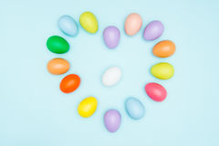 Oeufs de pâques colorés disposés dans la forme d'amour Photos stock