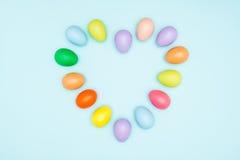 Oeufs de pâques colorés disposés dans la forme d'amour Images stock