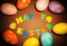 Oeufs de pâques colorés, inscription heureuse de Pâques et fleurs sur le Br Photographie stock libre de droits
