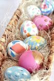 Oeufs de pâques colorés lumineux dans un nid en osier photos stock