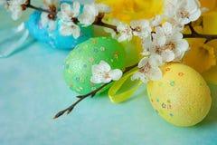 Oeufs de pâques colorés par pastel à côté de branche de floraison Images libres de droits