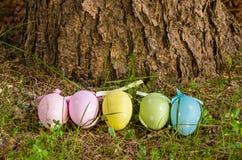 Oeufs de pâques colorés par pastel dans une rangée Beahind un tronc d'arbre Images stock