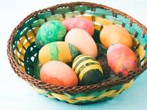 Oeufs de pâques colorés peints à la main par des enfants dans le panier Image stock