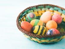 Oeufs de pâques colorés peints à la main par des enfants dans le panier Photos stock