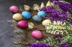 Oeufs de pâques colorés près du bouquet des fleurs sauvages Images libres de droits
