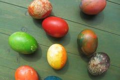 Oeufs de pâques colorés se trouvant sur le conseil en bois vert Photographie stock libre de droits