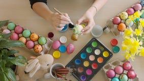Oeufs de pâques colorés sur la table Oeufs colorés par femme pour Pâques avec la brosse clips vidéos