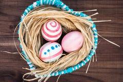 Oeufs de pâques colorés sur le fond en bois foncé rustique avec le nid et le panier bleu Foyer sélectif Photos stock