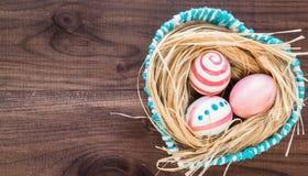 Oeufs de pâques colorés sur le fond en bois foncé rustique avec le nid et le panier bleu Foyer sélectif Photos libres de droits