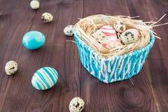 Oeufs de pâques colorés sur le fond en bois foncé rustique avec le nid et le panier bleu Foyer sélectif Photographie stock