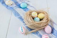 Oeufs de pâques colorés sur le fond en bois rustique blanc avec la serviette de nid et de toile Foyer sélectif Image stock