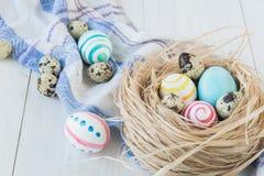 Oeufs de pâques colorés sur le fond en bois rustique blanc avec la serviette de nid et de toile Foyer sélectif Image libre de droits