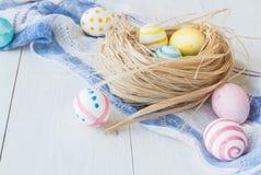 Oeufs de pâques colorés sur le fond en bois rustique blanc avec la serviette de nid et de toile Foyer sélectif Images stock