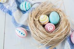 Oeufs de pâques colorés sur le fond en bois rustique blanc avec la serviette de nid et de toile Foyer sélectif Photographie stock