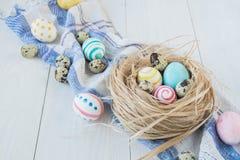 Oeufs de pâques colorés sur le fond en bois rustique blanc avec la serviette de nid et de toile Foyer sélectif Photographie stock libre de droits