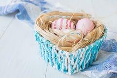 Oeufs de pâques colorés sur le fond en bois rustique blanc avec le nid et panier bleu sur le foyer sélectif de serviette de toile Photos stock