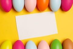 Oeufs de pâques colorés sur un fond jaune photos stock