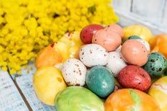 Oeufs de pâques colorés sur un plat blanc sous forme de coeurs et fleurs de mimosa sur une table en bois bleue Fin vers le haut Photos stock