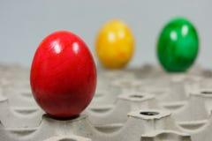 Oeufs de pâques colorés sur un plateau d'oeufs Photographie stock libre de droits
