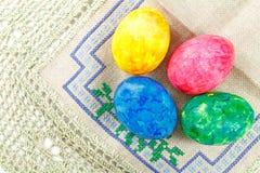 Oeufs de pâques colorés sur un tissu brut avec la broderie photo libre de droits